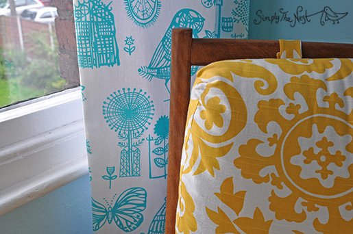 Turquoise curtains for a baby girl's nursery using Designer's Guild Boqueria fabric, plus a vintage upholstered Parker Knoll chair in Premier Prints yellow suzani fabric - a project by Simply The Nest, a UK DIY renovation blog