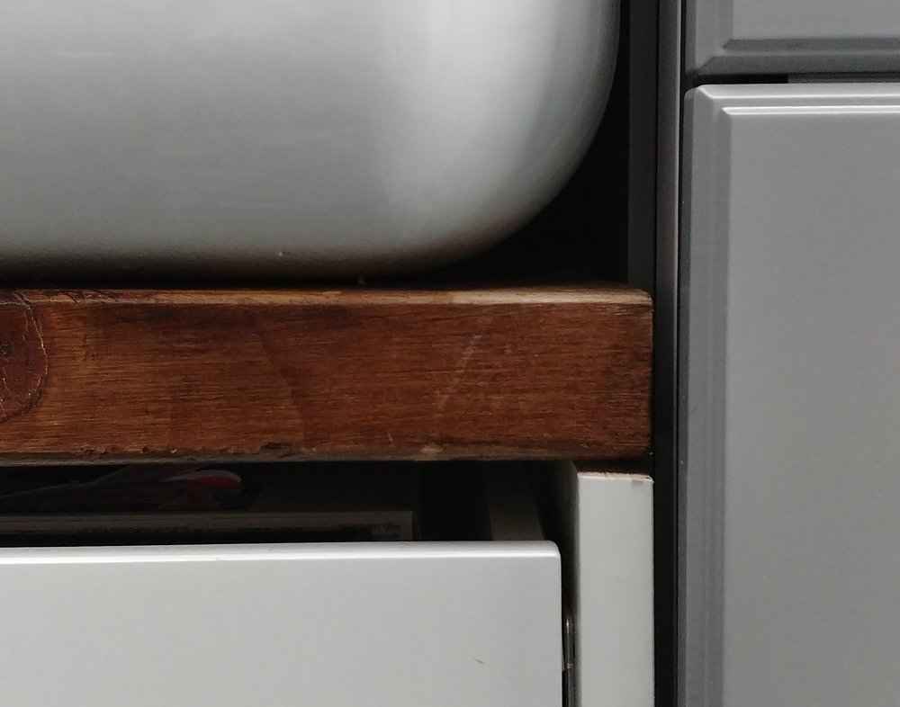 Close-up showing the wooden beam sitting on top of the cut-down sides of the sink cabinet. I pulled the drawer out to take this picture - normally the white drawer front and the rough edge of the cut-down side piece are covered.