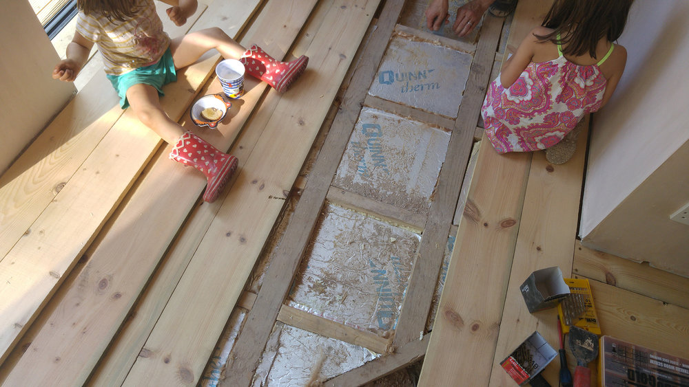 Laying the new (old) boards on top of the insulation board. Kids helping out as always.