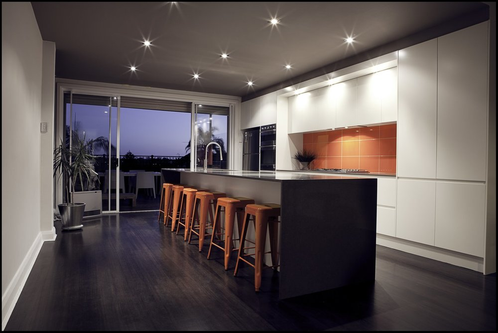 An eye-catching, red-tiled backsplash enlivens this kitchen.  Courtesy of Pablo Hiriyogen