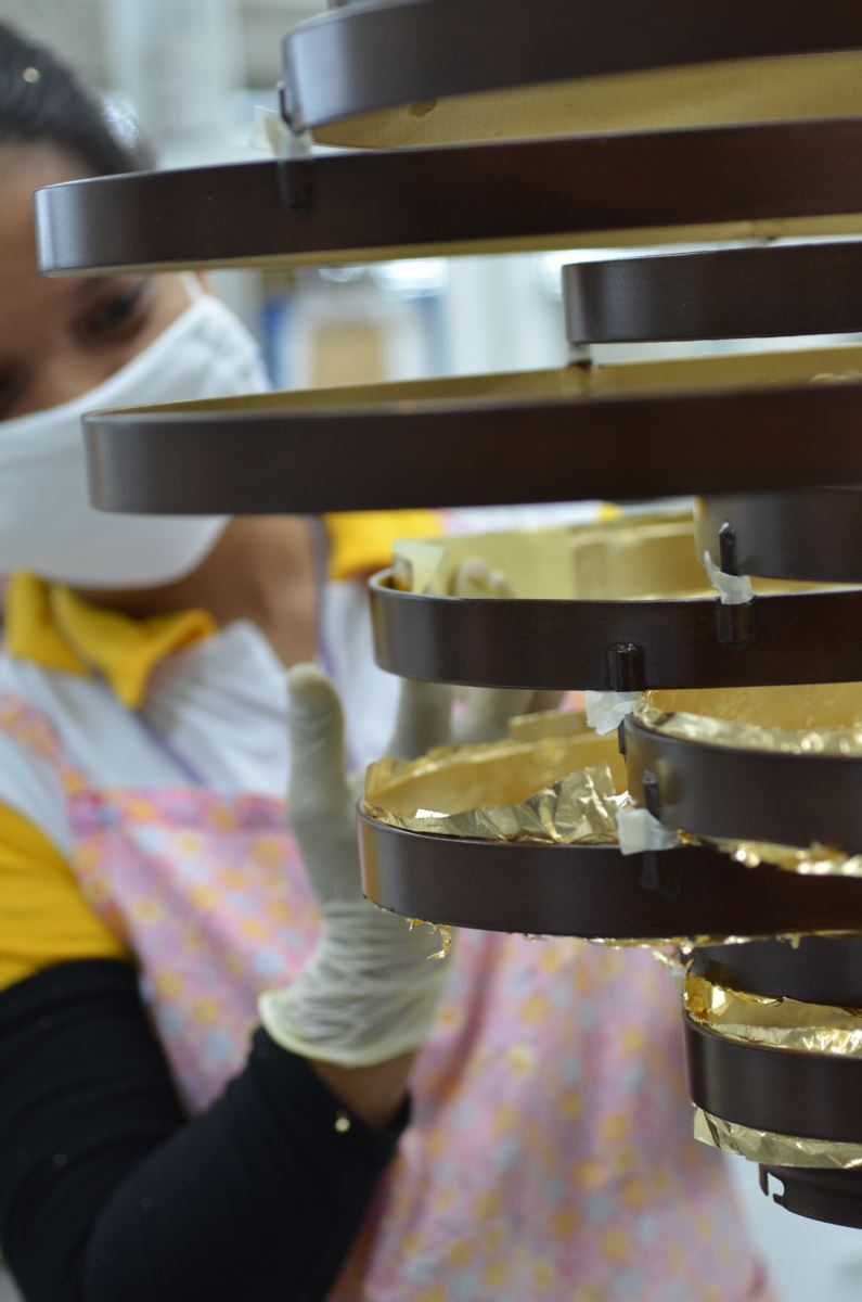 One of our artisans applies gold leaf to the inside of the large iron bands of our  Vertigo .