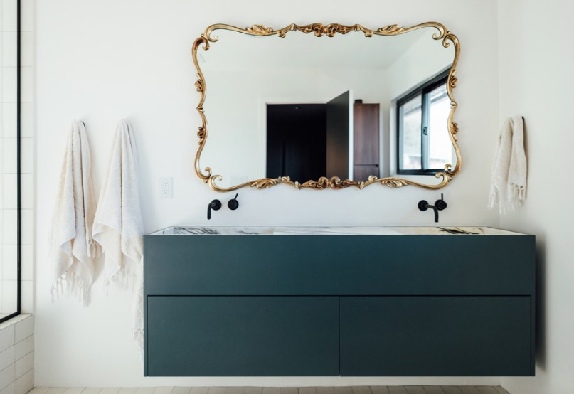 A subtle way to update your bathroom with the latest Color of the Year is by adding a single painted emerald green cabinet to a white bathroom. Image: City Home Collective