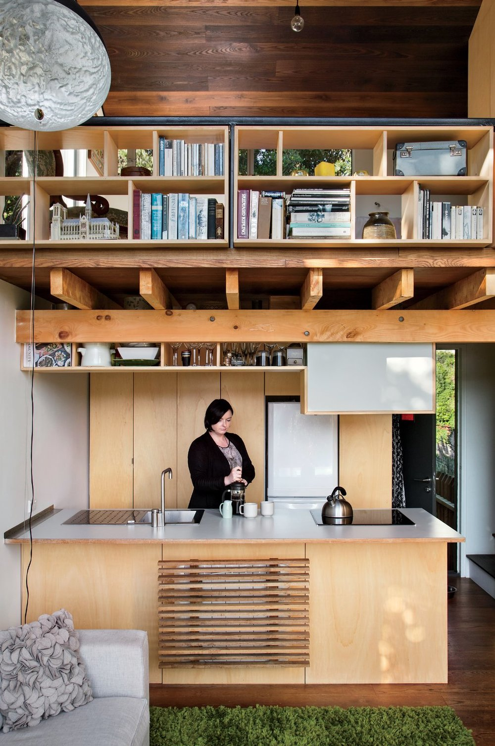 On the ground floor, Simpson's fiancée, Krysty Peebles, makes coffee in a compact kitchen outfitted with a Foraze Panni sink, Bosch induction cooktop, and Mitsubishi refrigerator.  Photo: Paul McCredie