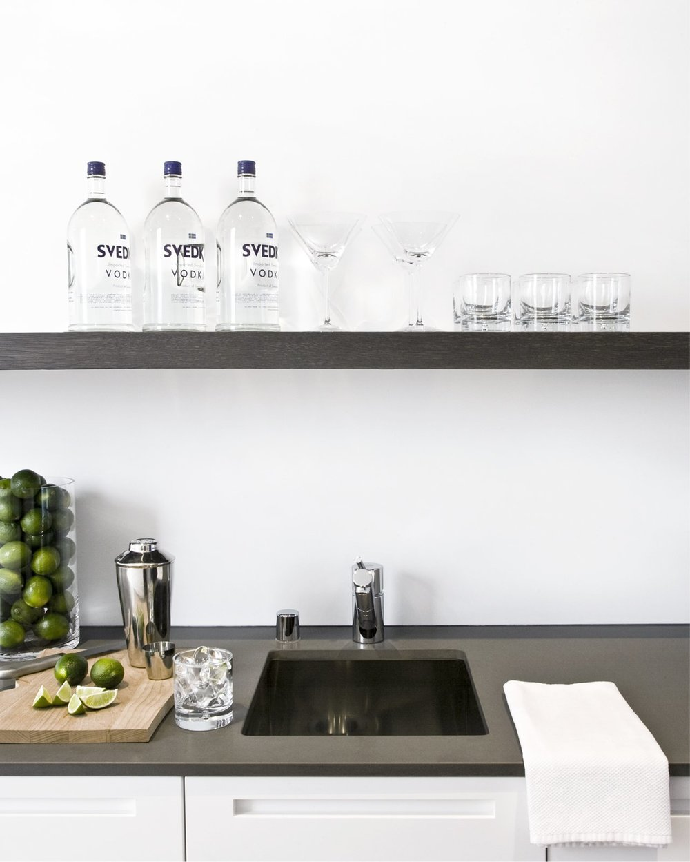 The wet bar at the end of the kitchen is equipped with a spout for filtered water, ice maker, wine fridge, and over-sink shelving—and is the happy-hour hotspot.  Ben Mayorga Photography
