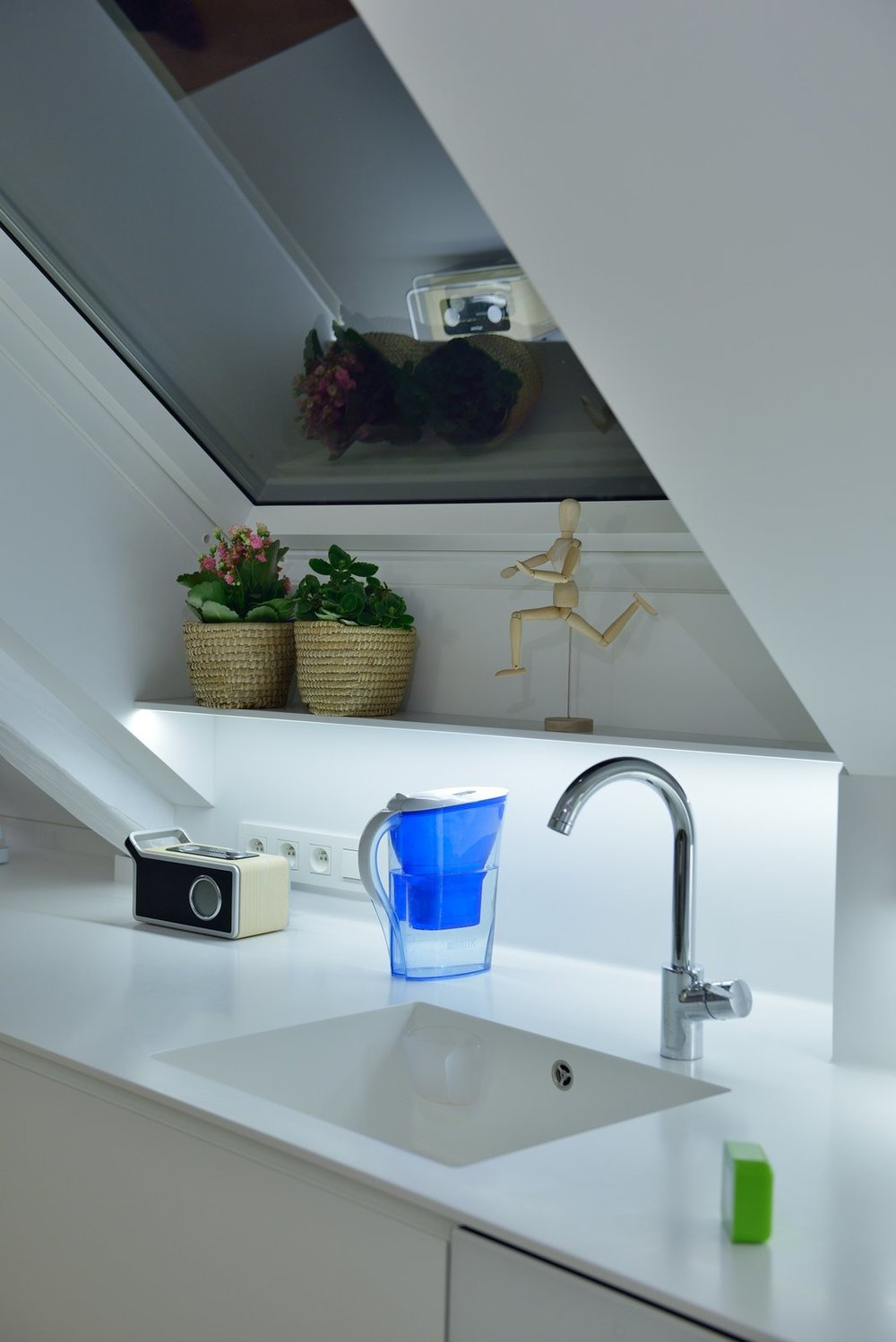 Detail of the kitchen desk with sink made of HI-MACS.  Courtesy of at26 architects