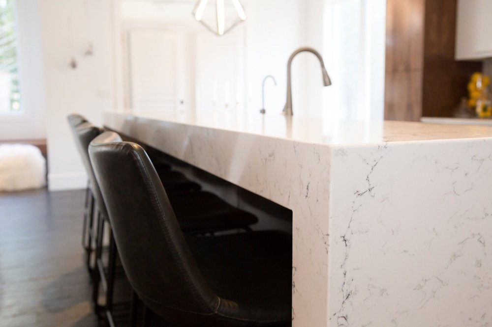 A close up of Caesarstone's 'White Attica,' a polished marble-like slab with delicate gray veining.  Stylin Homes- Allison Clark Photography