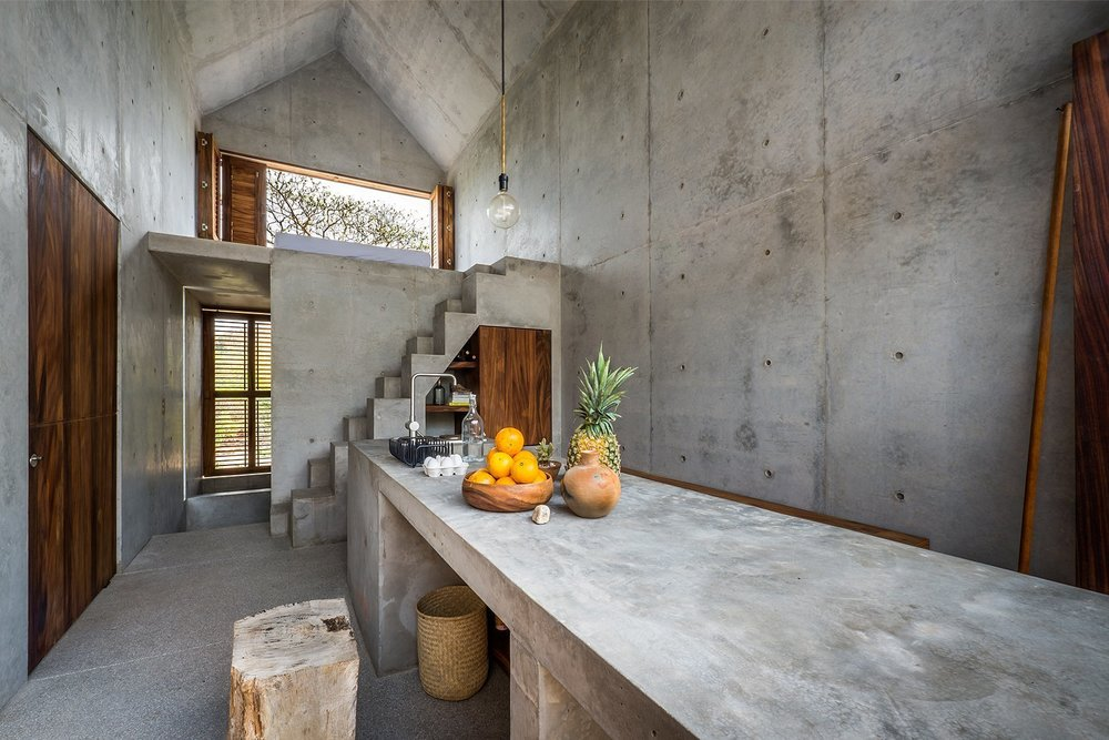 The concrete countertops, walls, and staircase echo the home's refined aesthetic.  Photo:  BoutiqueHomes