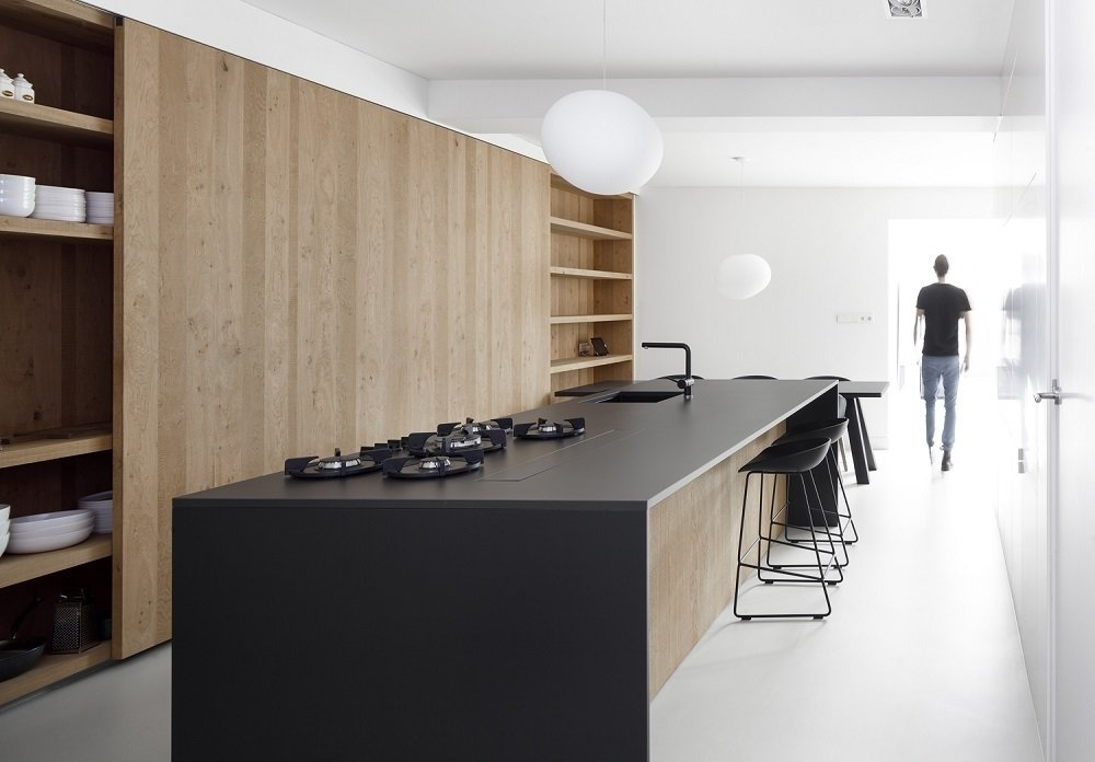 The kitchen island is made of oak with a thin, black stone countertop.  Photo Courtesy of Ewout Huibers