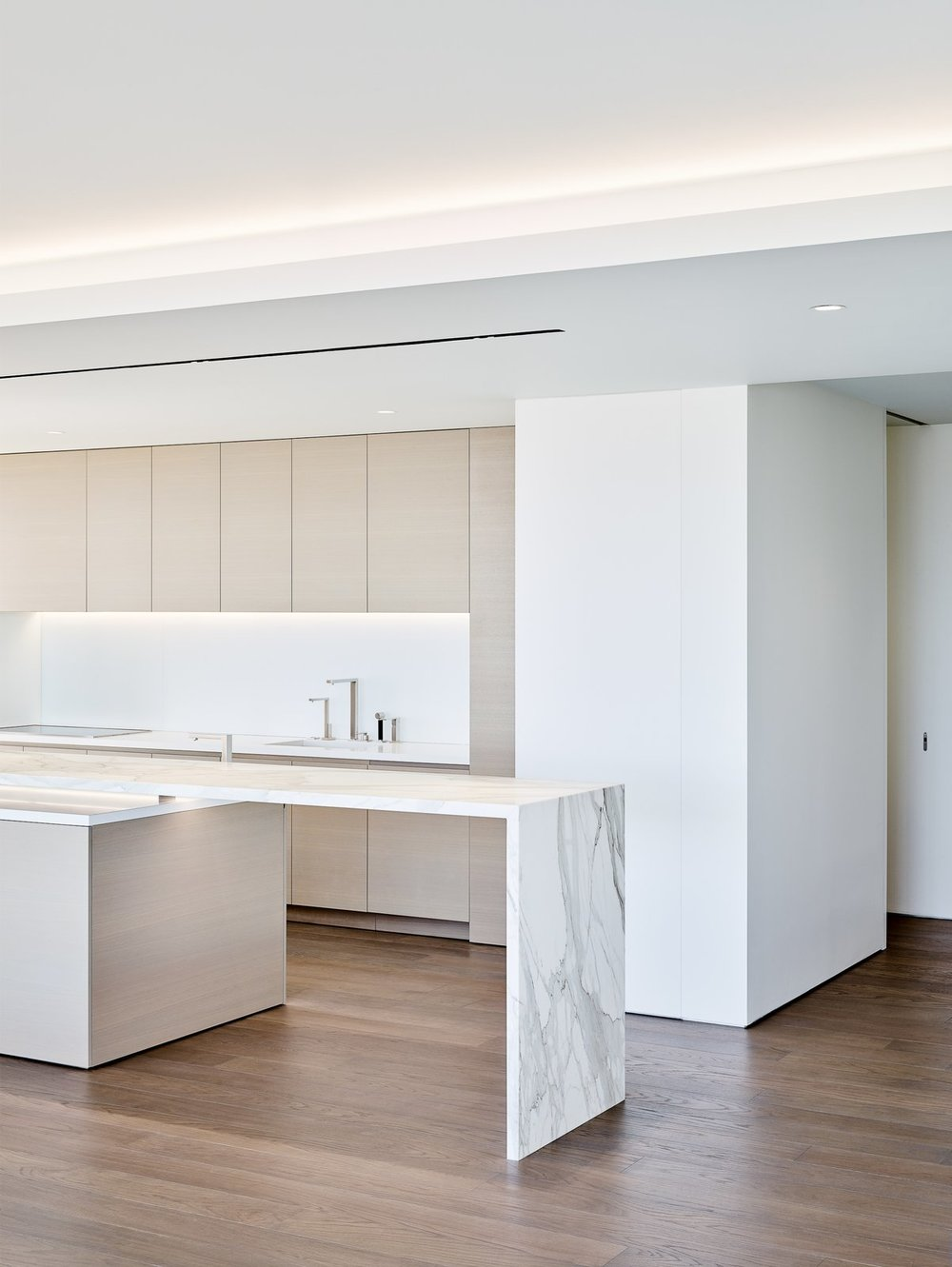 The crisp white kitchen features appliances built into the cabinetry and marble countertops.  Photo: Joe Fletcher