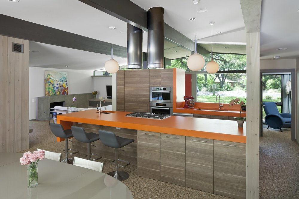 The architects went with a bold, orange hue for the kitchen countertops. Past the front door and a short hallway lies an expansive living, dining, and kitchen space.  Photo Courtesy of Andrea Calo