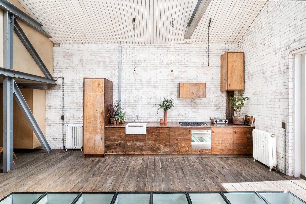 The kitchen area is full of charm, with cabinets made from reclaimed Iroko wood, incandescent lightbulb-style pendant lights hanging above the units, and a collection of potted house plants.  Photo Courtesy of The Modern House