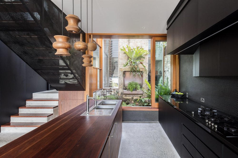 Large windows and floor-to-ceiling sliding doors have been integrated into the living space, providing an abundance of natural light, as well as easy access to the outdoor garden space. The perforated black walls are juxtaposed against warm wooden details like the countertop and pendant lights.  Photo:  Brett Boardman