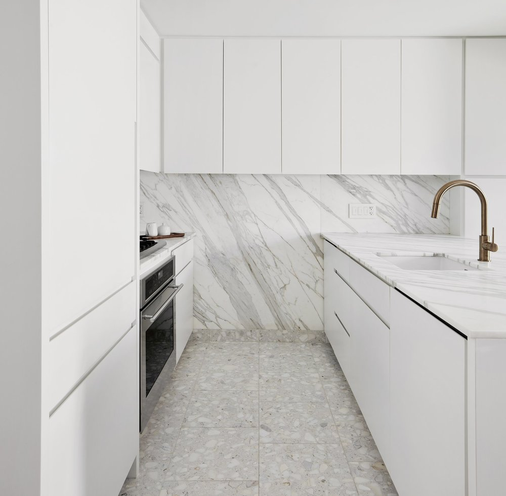 Because both Dale and Dan love to cook, and were intent on taking advantage of nearby Chelsea Market, the architect opened and significantly expanded the kitchen, adding a large counter topped by Calacatta Gold marble and installing a terrazzo tile floor with marble pieces that match the counter's creamy tone. He designed millwork to conceal and contain heating and cooling equipment along the window wall.  Photo by David Mitchell