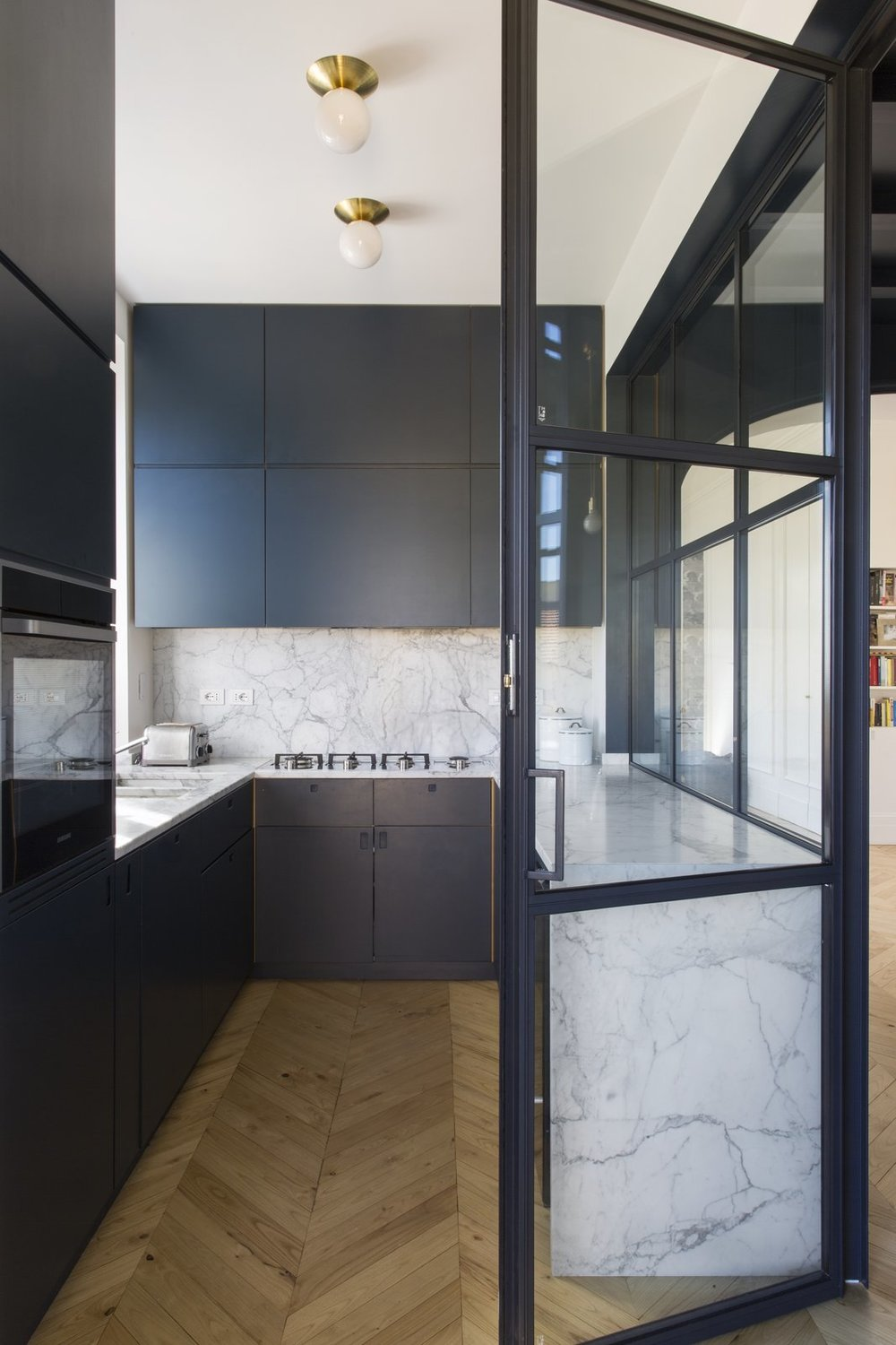 Crittall-style windows encase the sleek and modern kitchen. In this room, deep veined marble has been used for the counters and backsplash.  Photo Courtesy of Serena Eller