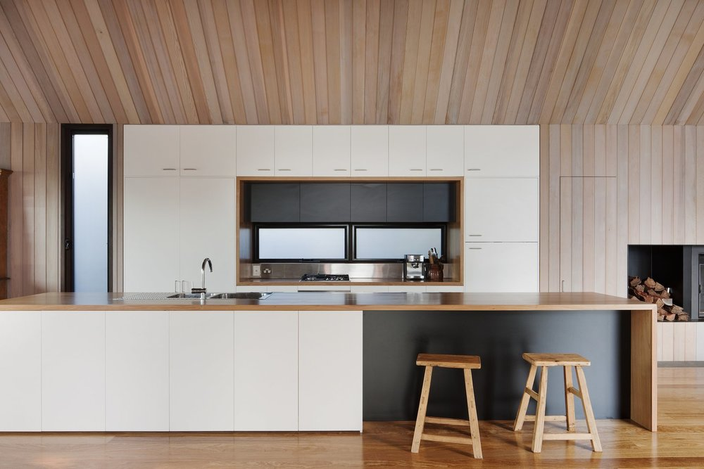 The streamlined kitchen is defined by its white cabinetry against the surrounding cedar walls, Ash wood floors, and wooden countertops.  Photo:  Shannon McGrath
