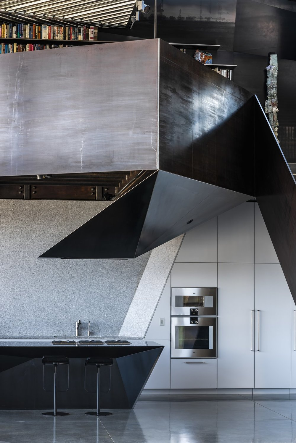 The glossy black and speckled gray counters of the kitchen mirror the rest of the home's incorporation of concrete and steel.  Photo:  Joe Fletcher