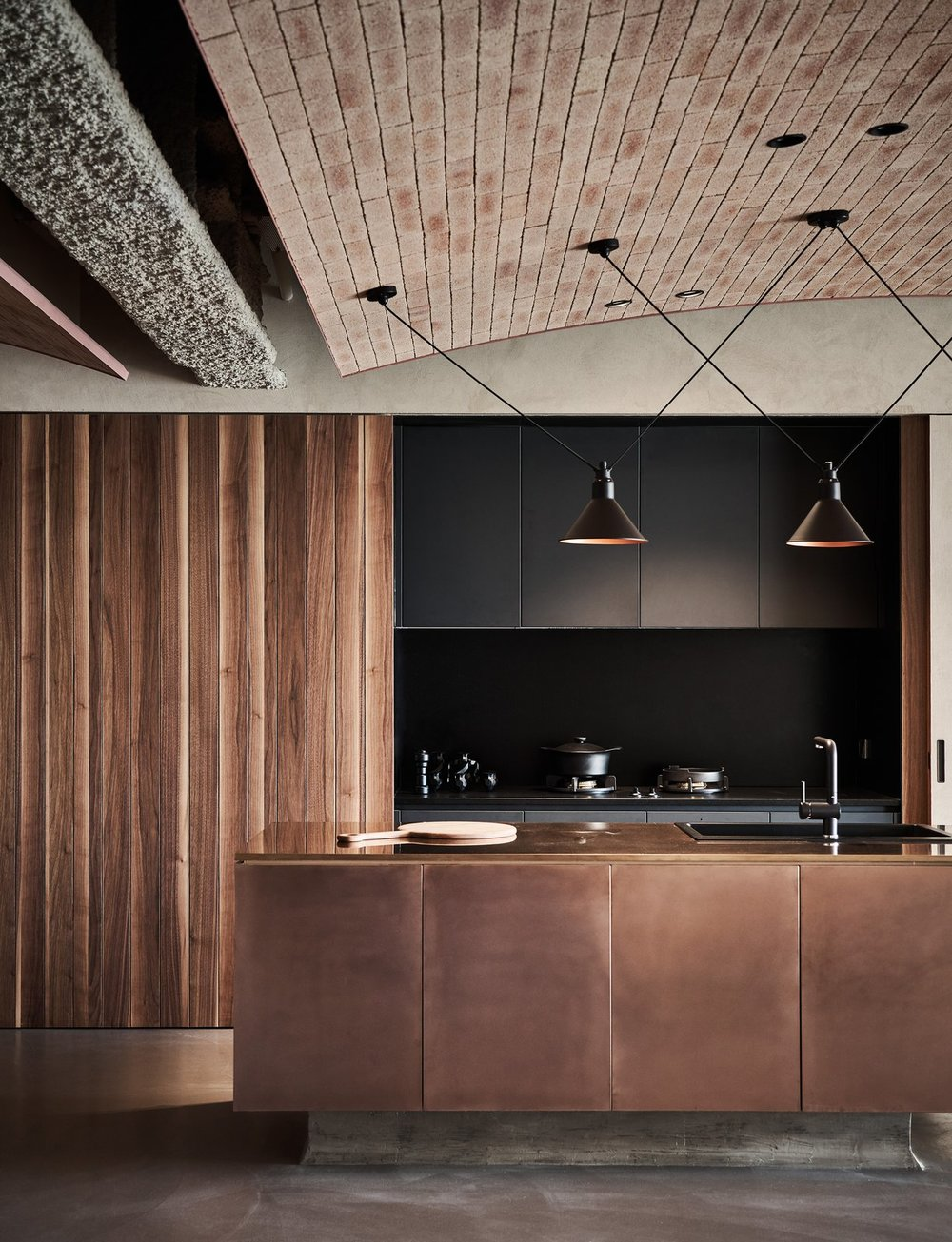 In the open kitchen, wood-paneled sliding doors conceal dark cabinetry, and together with a sleek, dark counter, and a shiny bronze-clad island with a sink, the kitchen becomes part of the overall design rather than simply an area of utility.  Photo Courtesy of Hey!Cheese