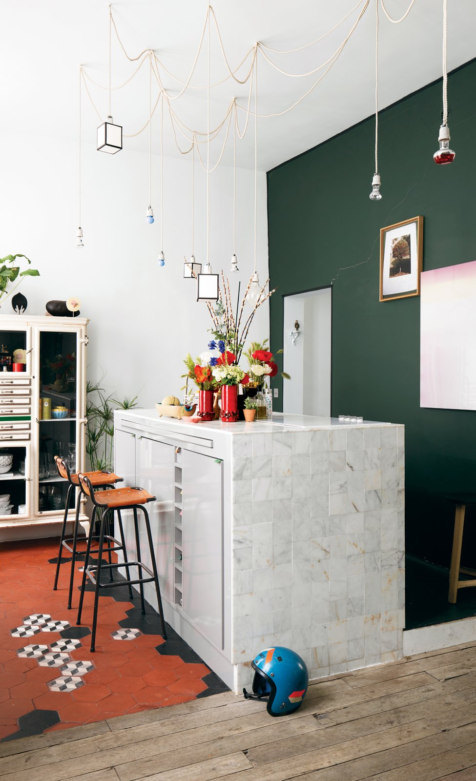 Homeowner Aumas designed the kitchen island, which is covered in marble tiles from Carrelages du Marais—the geometric floor tiles are from the same place—and strung the matrix of lights up above it.  Photo:  Christian Schaulin