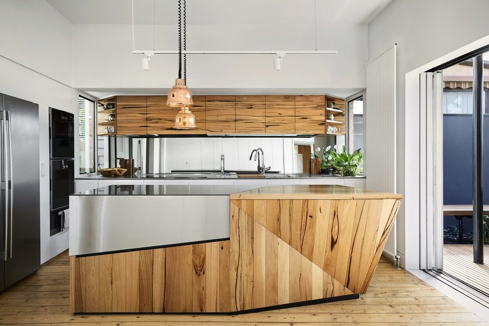 he kitchen cabinetry was fabricated using 100-year-old timber salvaged from Yarraville's sugar mills. The stainless-steel and timber island maximizes space with a secret hatch that opens to add extra surface area for food prep.    Photo by Tess Kelly