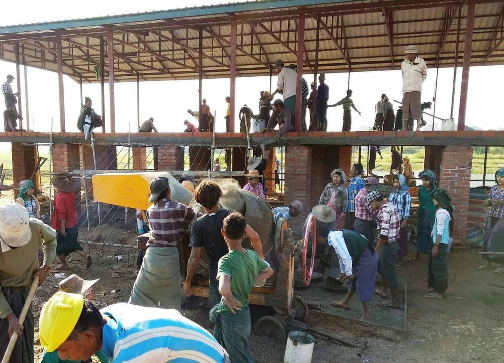 Villagers in Myanmar working together to build a better school