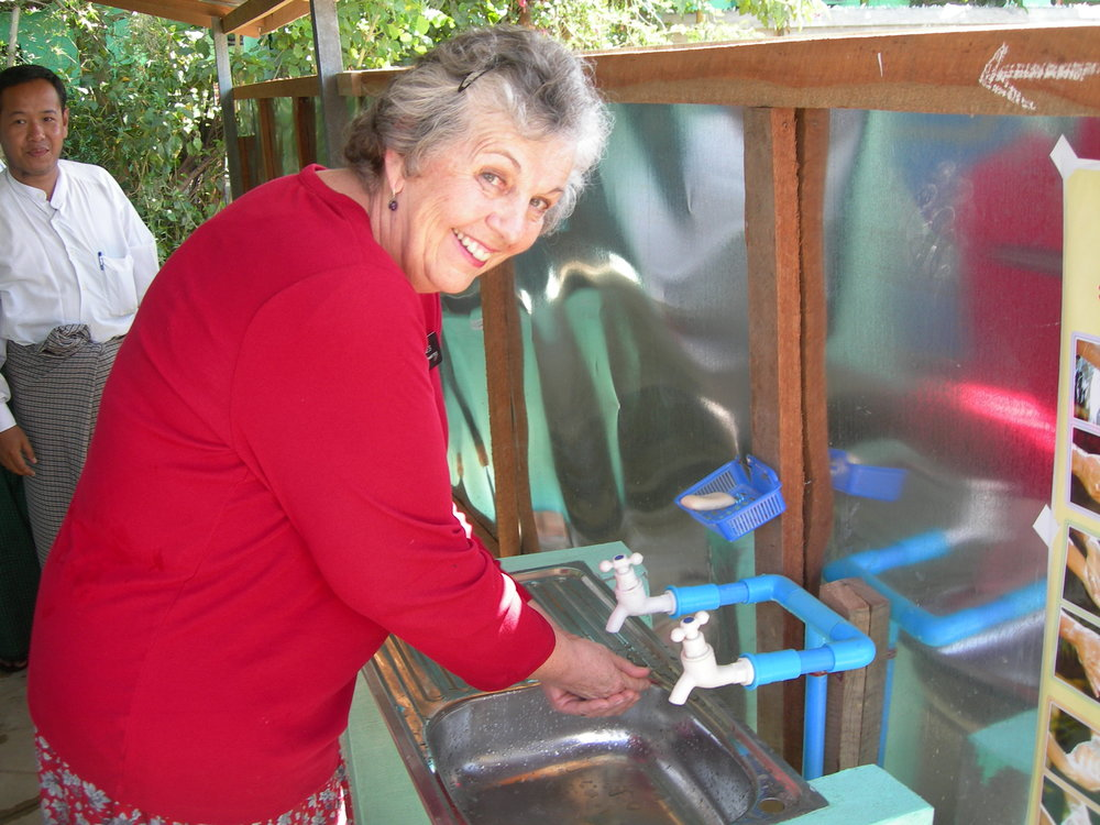Jayne Jones at a  new latrine: sinks & soap to wash  after using the latrines are a wonderful new development for this village