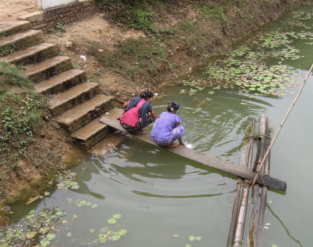 Without access to clean water sources, villagers draw water from a stagnant rainwater pond