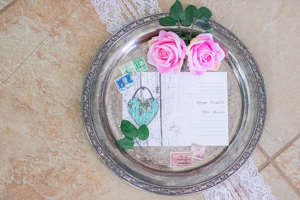 Rustic teal invitations with vintage stamps, silver tray, lace, pink roses and leaves.