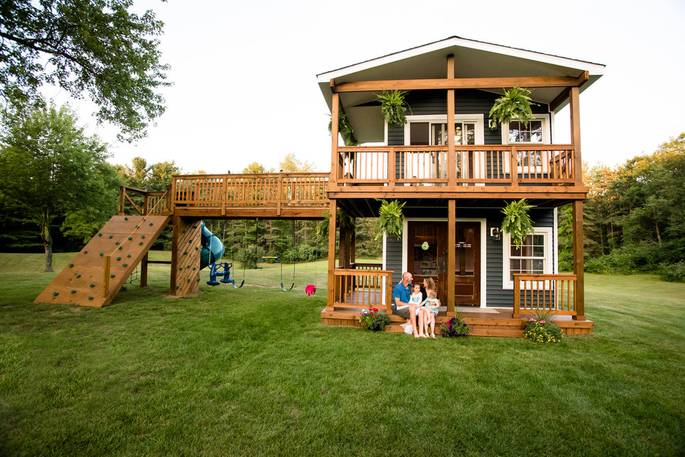 Details:   ·      42' wide, 22' tall   ·      Drywall   ·      Insulation   ·      Real windows   ·      Off-the grid electrical            -Low voltage electrical powered by solar panel Painted   ·      5/4 treated decking for wrap-around porch   ·      Treated handrail   ·      Bridge   ·      Rock climbing wall   ·      Swing set   ·      Standard height door   ·      Cherry live edge lumber and table  Price:    ·      $55,000, labor and material, for exact duplicate of the original Spoiled Rotten Homes playhouse   ·      Price does not include taxes and shipping   ·      Shipping cost varies based on location   ·      Playhouse can be built on-site if location is within 1 hour of Spoiled Rotten Homes   Disclaimer: if playhouse is being shipped, we recommend all painting be done at final location to prevent shipping damage.   We take great pride in the structural integrity and uniqueness of our playhouses.  All of our models are built just like a real house – full scale, 8-foot ceilings, and can be re-purposed into a guest house, she-shed, or man-cave when the kids are all grown up and moved out!  Our playhouses stand the test of time!