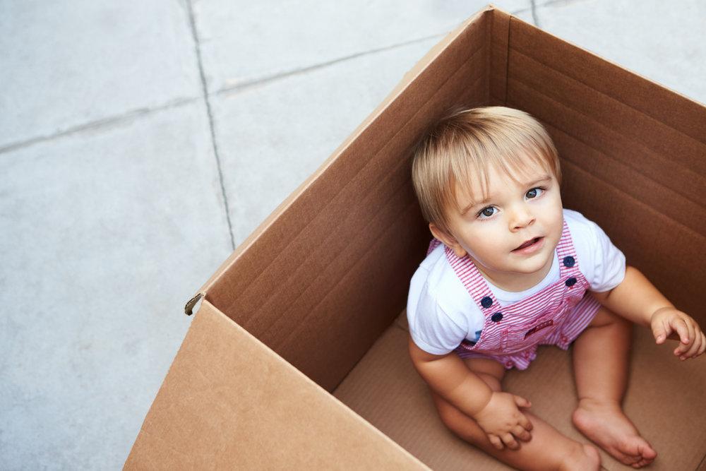little-boy-playing-inside-moving-in-box-PL5F68U.jpg