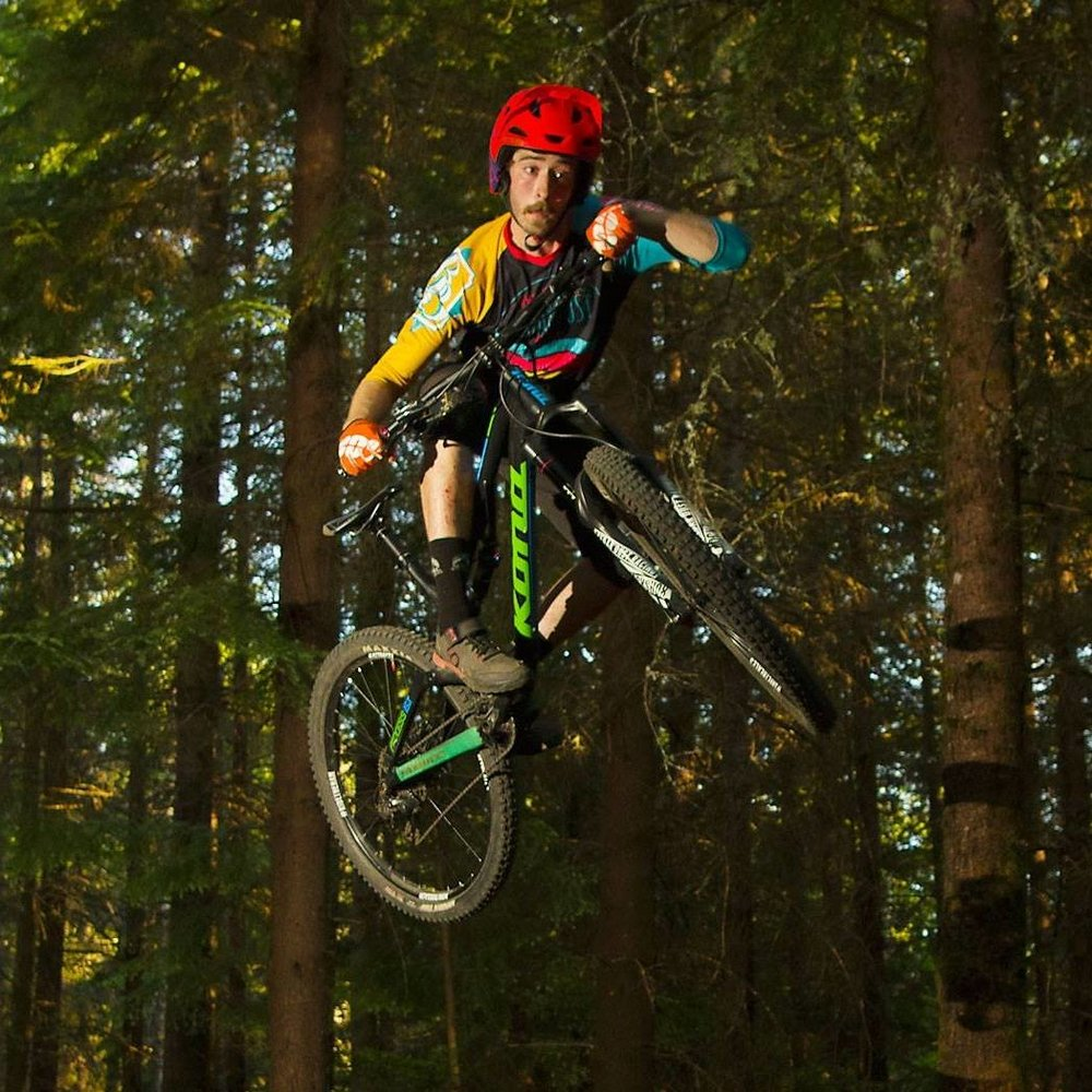 FORREST IN THE TREES   I grew up in Port Townsend WA, an hour and a half South of Bellingham, on the Olympic Peninsula. Raised on camping trips and exploring the woods, I quickly became attached to mountain bikes once I had access to them in sixth grade. My passion quickly grew and I began racing in High School. Discovering a new (competitive) side to the sport that had taken over my focus was a huge moment for me. I moved to Bellingham after High School to pursue a four year degree at WWU & dedicate myself to the Mountain Bike Lifestyle.  More often than not you can find me in the woods. Most of my riding is done at Galbraith Mountain due to the ease of access & sheer amount of world class trails in one zone, that being said, Bellingham has numerous trail.  My favorite local ride is in the Chuckanut Mountains at Larrabee State Park. This ride starts out above Clayton Beach at the Fragrance Lake Trail Head. The pedal up to the top of the mountain is about 4 miles long with around 1800ft of elevation gain. At the top you are rewarded with a stunning view of the Puget Sound & San Juan Islands.  My favorite way to get back to the bottom is the most direct. Two trails by the names of Double Black & Double Down, each a mile long, are some of the most raw and exciting trails in the county. As a part of the Boundary Bay Adventures I represent Cedar Dust Racing, named after an Iconic Galbraith Trail & IPA brewed here at the Brewery.