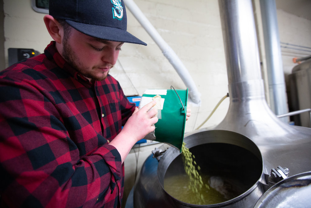Army Veteran and bartender, Sam Stringer helps pour the hops for the Gratitude IPA.