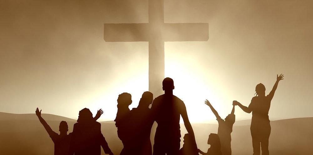 family gathered around cross to worship.jpg
