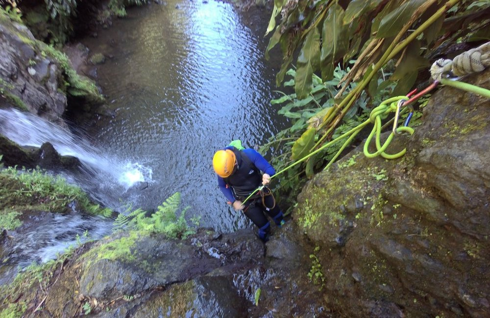 Abseiling down a waterfall during the canyoning experience.