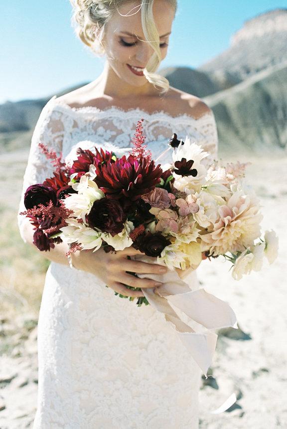 A desert wedding bouquet of dahlias, astilbe, chocolate cosmos, lace cap hydrangea, ranunculus,garden roses, and blushing bride   Photo by  Kaylan Robinson