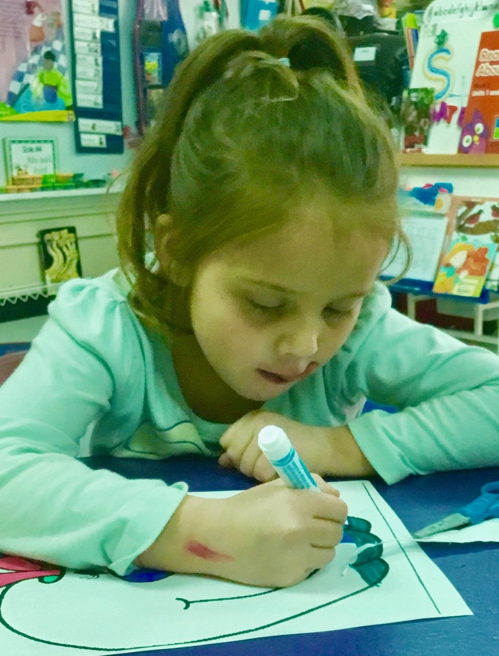A budding artist works hard with donated supplies.