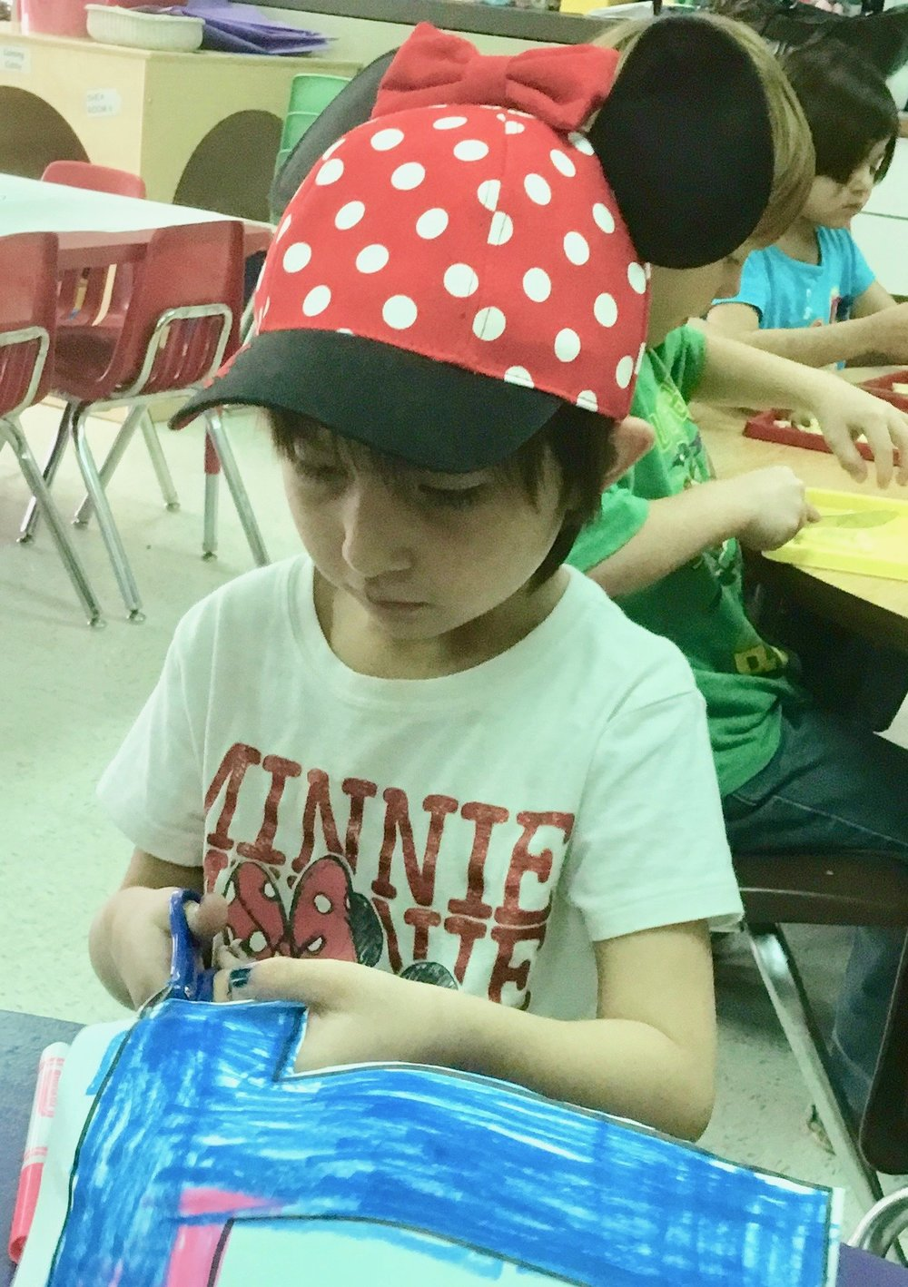 A pre-K Minnie Mouse enthusiast shows off her skills with a scissors.