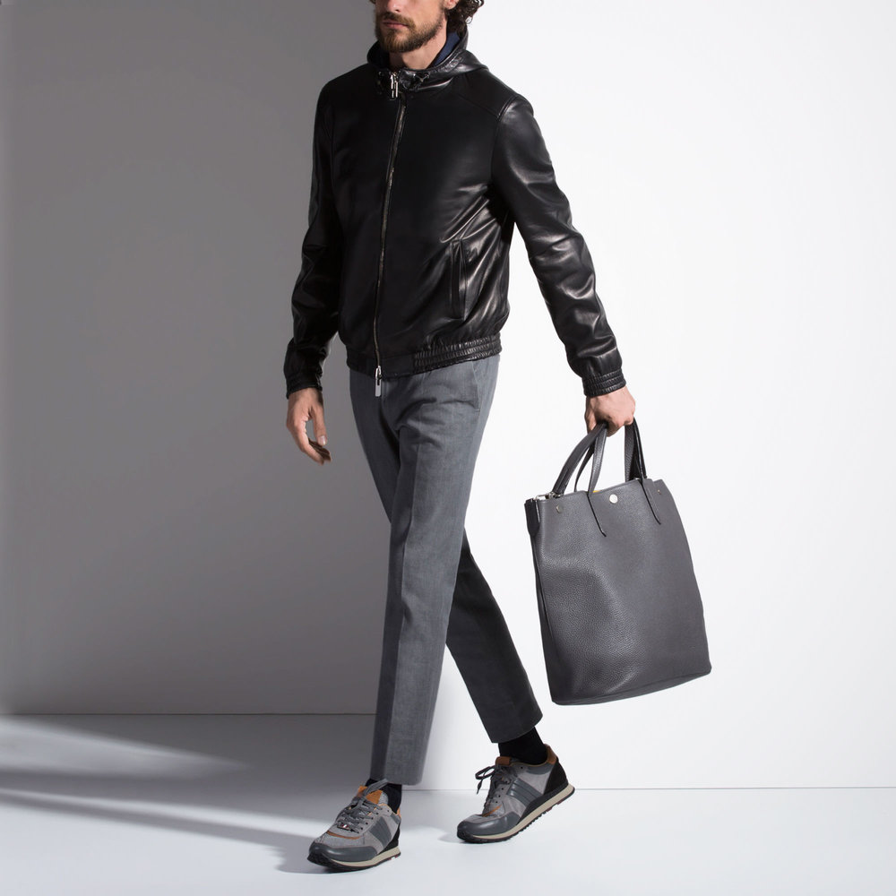 A man wearing a leather jacket and holding a leather briefcase.