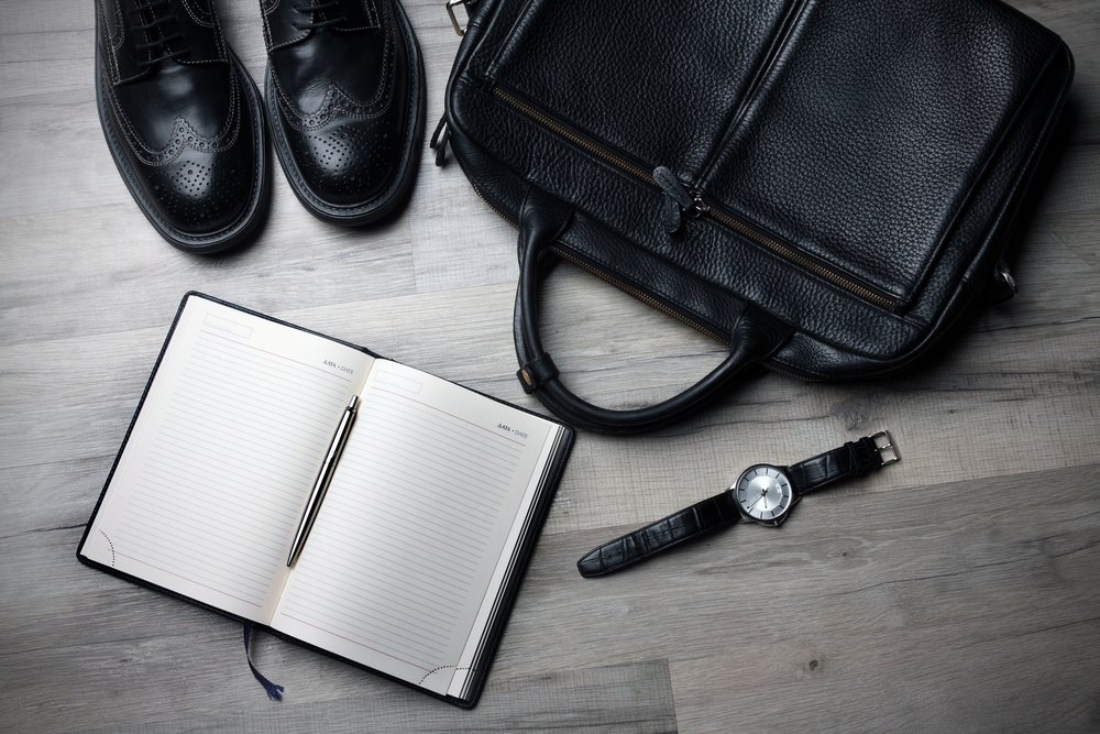 A display of black leather dress shoes, briefcase, notepad, and watch strap.