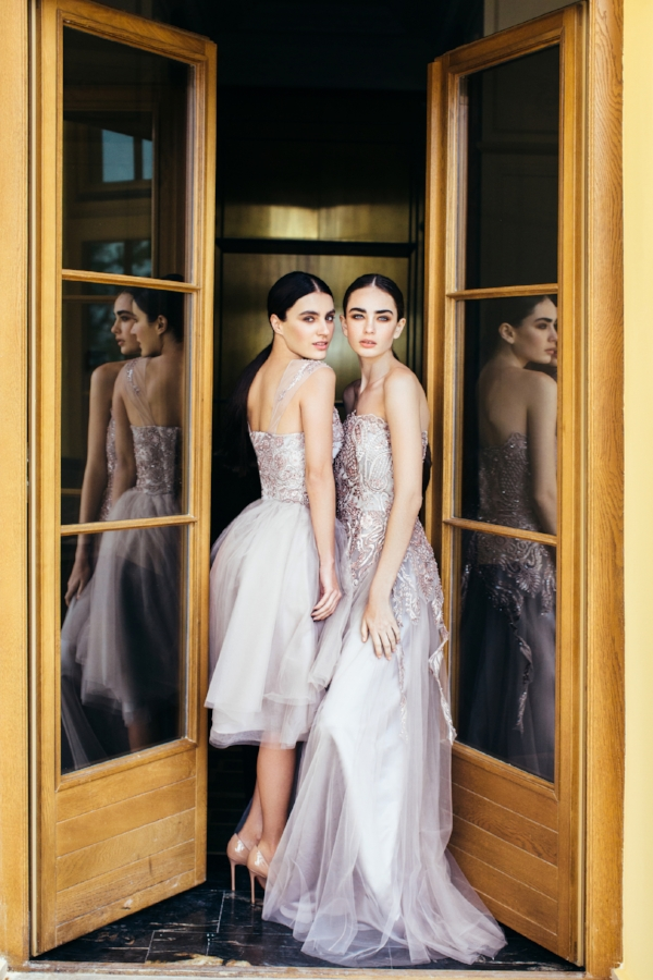 Two bridesmaids standing in doorway, dressed in matching white gowns.