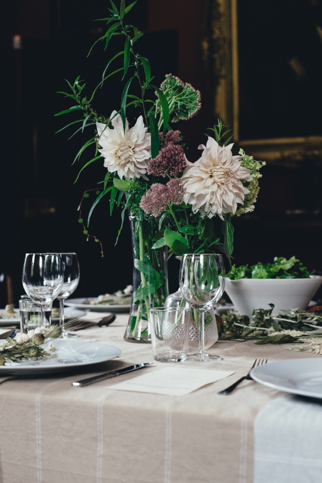 A fully arranged holiday dinner spread with crystals, flower vases, plates, and silverware.
