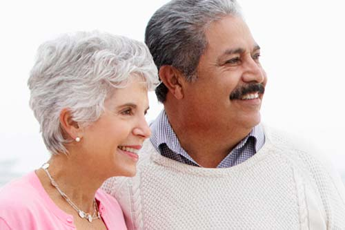elderly couple smiling next to each other looking into the distance