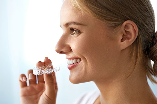 Beautiful woman smiling about to insert a clear tooth aligner into her mouth