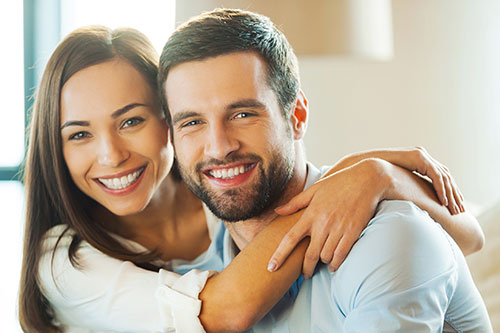 young couple smiling and hugging looking at camera early in the morning