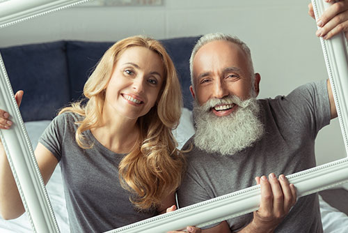 smiling middle age couple holding frame on bed