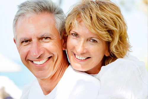 middle aged couple, woman giving back hug and smiling at camera