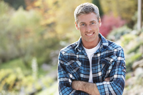 middle aged man outdoors arms crossed smiling at camera