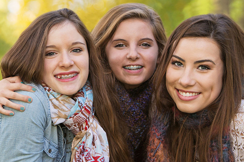 three teen girls hugging and smiling