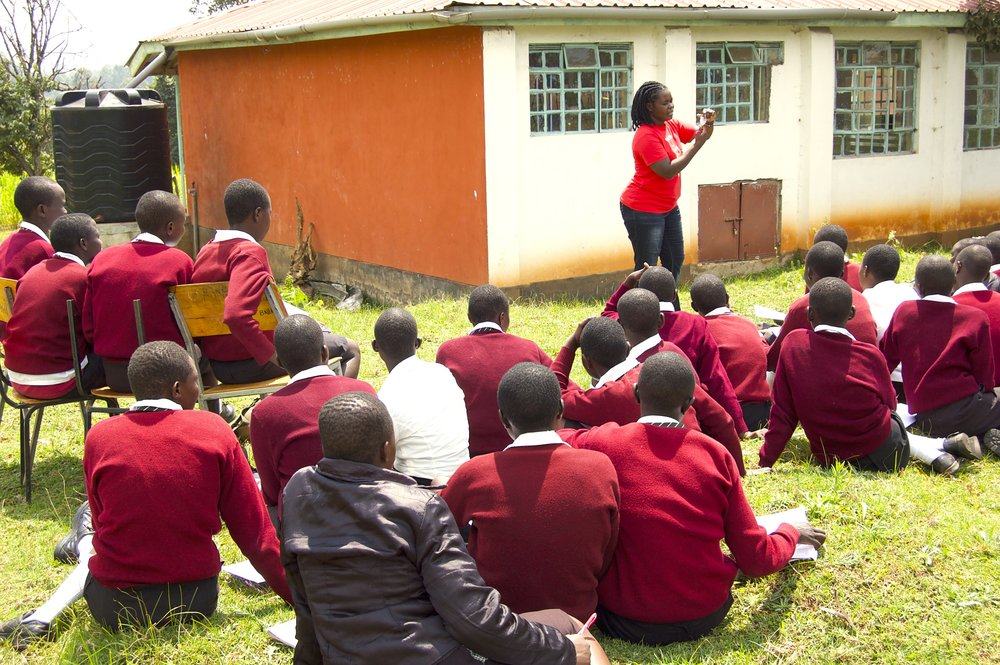 Golda, from Golden Girl Foundation, reveals the menstrual cup to a group of girls at Shoe4Africa Martin Lel Secondary School.
