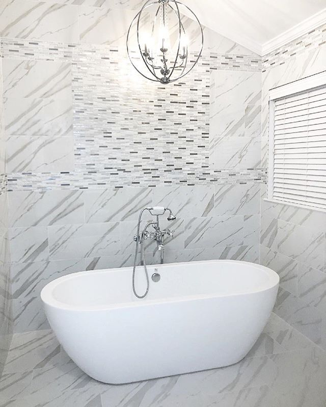 A regal marble-look porcelain with a mosaic glass and stone border fills this large Master Bathroom with crisp sophistication. ✨ | #porcelain #masterbathroom #bathroomsofinstagram #monseyny #ceramiccreations