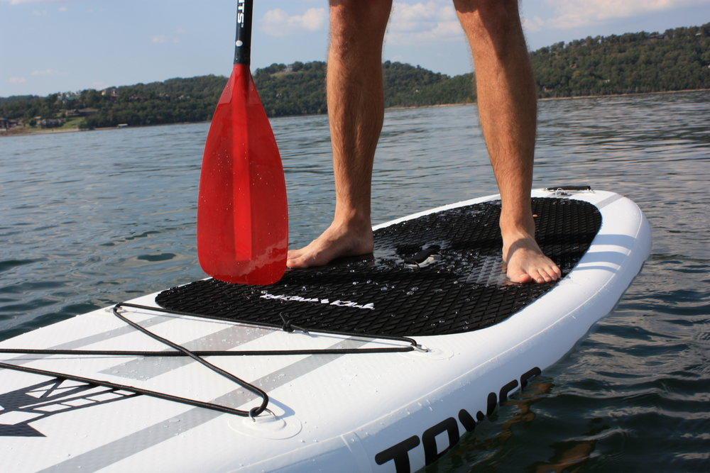 """Tower Inflatable SUPs - All the performance of a plastic/epoxy SUP but with none of the transportation headaches! Each Tower SUP rolls up into a compact bundle that will fit in any vehicle. When you arrive at your destination, simply unroll the SUP, attach the pump to the grey valve in the rear, and air it up to between 10-15 PSI. You'll be standing on air, but won't even know it! Includes a hand-pump, which takes 5-10 minutes to inflate the SUP to capacity. We also have a car-charger powered electric pump for rent for an additional change. When your day on the water is finished, simply deflate the sup, roll it up from the bow to the stern, and attach the storage strap. Adventurer 1 iSUP (Length: 9'10"""", Weight: 24 lbs, Weight capacity: 300 lbs) Adventurer 2 iSUP (Length: 10'4"""", Weight: 25 lbs, Weight capacity: 350 lbs)"""